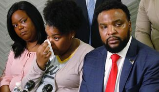 Amber Carr, center, wipes a tear as her sister, Ashley Carr, left, and attorney Lee Merritt, right, listen to their brother Adarius Carr talk about their sister, Atatiana Jefferson during a news conference Monday, Oct. 14, 2019 in downtown Dallas. The family of the 28-year-old black woman who was shot and killed by a white police officer in her Fort Worth home as she played video games with her 8-year-old nephew expressed outrage that the officer has not been arrested or fired. (Irwin Thompson/The Dallas Morning News via AP)