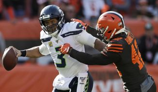 Seattle Seahawks quarterback Russell Wilson (3) avoids Cleveland Browns strong safety Morgan Burnett (42) during the second half of an NFL football game, Sunday, Oct. 13, 2019, in Cleveland. (AP Photo/Ron Schwane)