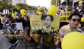 """Pro-government supporters hold signs with pictures of Justice Minister Cho Kuk, before a rally supporting Cho in front of Seoul Central District Prosecutors' Office in Seoul, South Korea, Saturday, Oct. 12, 2019. Tens of thousands of government supporters gathered in South Korea's capital for the fourth straight Saturday to show their support for President Moon Jae-in's justice minister, who is enmeshed in an explosive political scandal that has polarized the nation. The letters read """"Reform the Prosecution"""" and """"Protect Cho Kuk"""". (AP Photo/Lee Jin-man)"""