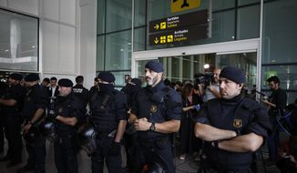 Police officers stand by a doorway as protestors try to block access to El Prat airport in Barcelona, Spain, Monday, Oct. 14, 2019. Spain's Supreme Court on Monday convicted 12 former Catalan politicians and activists for their roles in a secession bid in 2017, a ruling that immediately inflamed independence supporters in the wealthy northeastern region. (AP Photo/Emilio Morenatti)