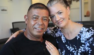 Donaldo Morales, left, and his wife Isleen Gimenez Morales, right, pose for a photograph at an attorney's office in Kansas City, Mo., Tuesday, Sept. 17, 2019. (AP Photo/Orlin Wagner)