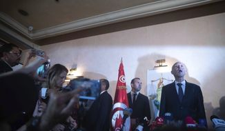 Tunisian law professor Kais Saied speaks to the reporters and supporters Sunday, Oct. 13, 2019 in Tunis. Kais Saied looked set to assume Tunisia's presidency after polling agencies suggested he overwhelmingly won Sunday's runoff election in the country that unleashed the Arab Spring pro-democracy uprisings. (AP Photo/Mosa'ab Elshamy)