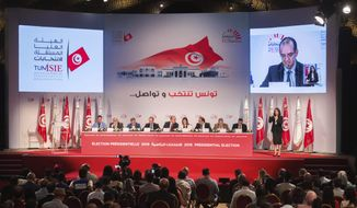 The Independent High Electoral Commission announces the results of the presidential election in Tunisia, Monday, Oct. 14, 2019. Tunisia's electoral body said official preliminary results show that conservative, Islamist-backed law professor Kais Saied has largely won the presidential election.  (AP Photo/Mosa'ab Elshamy)