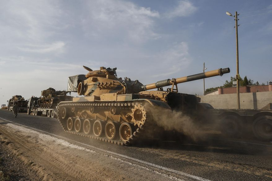 A Turkish forces tank is driven to its new position after was transported by trucks, on a road towards the border with Syria in Sanliurfa province, Turkey, on Monday, Oct. 14, 2019. Syrian troops entered several northern towns and villages Monday, getting close to the Turkish border as Turkey's army and opposition forces backed by Ankara marched south in the same direction, raising concerns of a clash between the two sides as Turkey's invasion of northern Syria entered its sixth day. (AP Photo/Emrah Gurel)