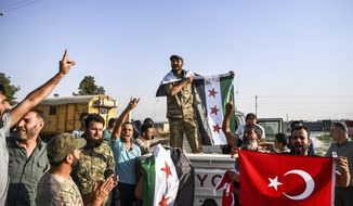 Turkish-backed Syrian opposition fighters celebrate in Akcakale, in Sanliurfa province advance, after entering over the border from Tal Abyad, Syria, Sunday, Oct. 13, 2019. State-run Anadolu news agency reported Tal Abyad had fallen to a Turkish military offensive on Sunday.  (AP Photo/Cavit Ozgul)