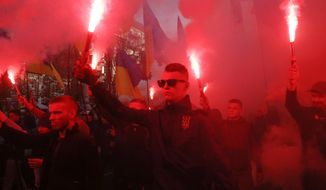 """Members of the nationalist movements light flares during a rally marking Defense of the Homeland Day in center Kyiv, Ukraine, Monday, Oct. 14, 2019. Some 15,000 far-right and nationalist activists protested in the Ukrainian capital, chanting """"Glory to Ukraine"""" and waving yellow and blue flags. President Volodymyr Zelenskiy urged participants to avoid violence and warned of potential """"provocations"""" from those who want to stoke chaos. (AP Photo/Efrem Lukatsky)"""