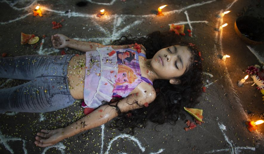 In this photo taken Oct. 13, 2019, girl lies surrounded by candles and designs of white powder during a ceremony on Sorte Mountain where followers of indigenous goddess Maria Lionza gather annually in Venezuela's Yaracuy state. Believers congregated for rituals on the remote mountainside where adherents make an annual pilgrimage to pay homage to the goddess, seeking spiritual connection and physical healing. (AP Photo/Ariana Cubillos)