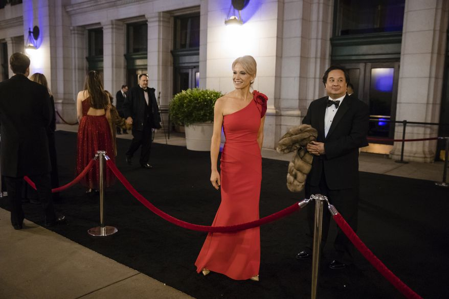 In this Thursday, Jan. 19, 2017, file photo, President-elect Donald Trump's adviser Kellyanne Conway, center, accompanied by her husband, George, speaks with members of the media as they arrive for a dinner at Union Station in Washington, the day before Trump's inauguration. (AP Photo/Matt Rourke) ** FILE **