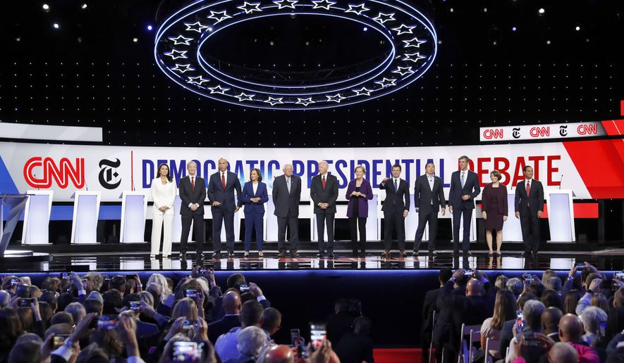 From left, Democratic presidential candidates, Rep. Tulsi Gabbard, D-Hawaii, businessman Tom Steyer, Sen. Cory Booker, D-N.J., Sen. Kamala Harris, D-Calif., Sen. Bernie Sanders, I-Vt., former Vice President Joe Biden, Sen. Elizabeth Warren, D-Mass., South Bend Mayor Pete Buttigieg, entrepreneur Andrew Yang, former Texas Rep. Beto O'Rourke, Sen. Amy Klobuchar, D-Minn., and former Housing Secretary Julian Castro stand on stage for a photo before a Democratic presidential primary debate hosted by CNN and The New York Times at Otterbein University, Tuesday, Oct. 15, 2019, in Westerville, Ohio. (AP Photo/John Minchillo)