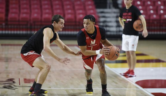 Maryland NCAA college basketball player Anthony Cowan Jr., right, and Reese Mona practice drills during Media Day, Tuesday, Oct. 15, 2019, in College Park, Md. (AP Photo/Gail Burton)