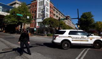 Montgomery police officer block the intersection where a parking garage is seen, where a police officer was shot, in downtown Silver Spring, Md., Monday, Oct. 14, 2019.  Police in Montgomery County, Maryland, said they were searching for at least one person after an officer was found shot in a parking garage in downtown Silver Spring on Monday. (AP Photo/Jose Luis Magana)