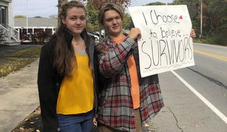 In this Monday, Oct. 7, 2019, photo provided by Shael Norris, high school sophomore Aela Mansmann, 15, of Cape Elizabeth, Maine, left, stands with her brother Aidan, 13, as he displays a placard during a school walkout, in Cape Elizabeth. The American Civil Liberties Union of Maine is calling on a federal court to stop the suspension of Aela Mansmann who accused an unnamed person of sexual assault. Aela and Aidan participated in the school walkout meant to protest the suspension of Aela and two other students. (Shael Norris via AP)