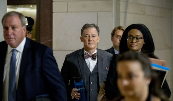 Deputy Assistant Secretary of State George Kent, center, arrives on Capitol Hill in Washington, Tuesday, Oct. 15, 2019, as he is scheduled to testify before congressional lawmakers as part of the House impeachment inquiry into President Donald Trump. (AP Photo/Andrew Harnik)
