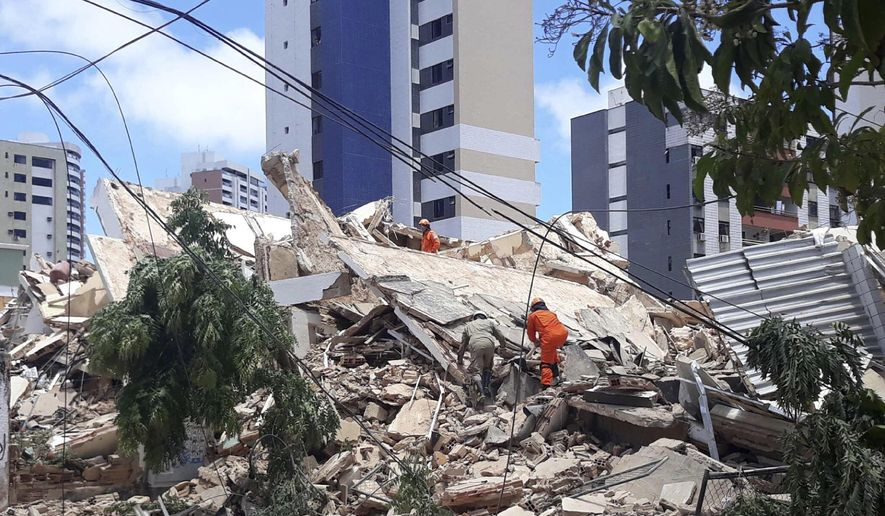 Firefighters search for people who are trapped after a building collapsed in Fortaleza, Ceara state, Brazil, Tuesday, Oct. 15, 2019. A seven-story building collapsed Tuesday in the northeastern city of Fortaleza, killing at least one person. City authorities informed several others are under the debris, and some of them are communicating with relatives and rescue teams by telephone. (LC Moreira/Futura Press via AP)