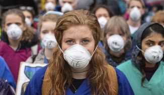 Doctors gather to protest in support of Extinction Rebellion (XR) at Jubilee Gardens, London, Saturday Oct. 12, 2019, to highlight deaths caused by air pollution. Environmental protests have been taking place in cities around the world. (Dominic Lipinski/PA via AP)