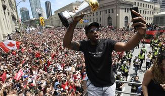 FILE - In this June 17, 2019, file photo, then Toronto Raptors forward Kawhi Leonard takes a photo while holding his playoffs MVP trophy during the NBA basketball championship team's victory parade in Toronto. The NBA's balance of power has shifted to the Los Angeles Clippers, who have never advanced beyond the second round let alone won a championship. All that is expected to change behind Leonard and Paul George, both regarded as two of the best two-way players in the league. (Frank Gunn/The Canadian Press via AP, File)