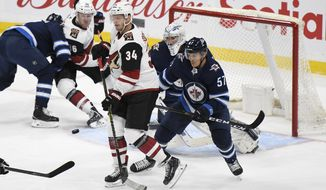 Winnipeg Jets' Gabriel Bourque (57) and Arizona Coyotes' Carl Soderberg (34) watch as the puck is shot toward Jets goalie Connor Hellebuyck during the first period of an NHL hockey game Tuesday, Oct. 15, 2019, in Winnipeg, Manitoba. (Fred Greenslade/The Canadian Press via AP)