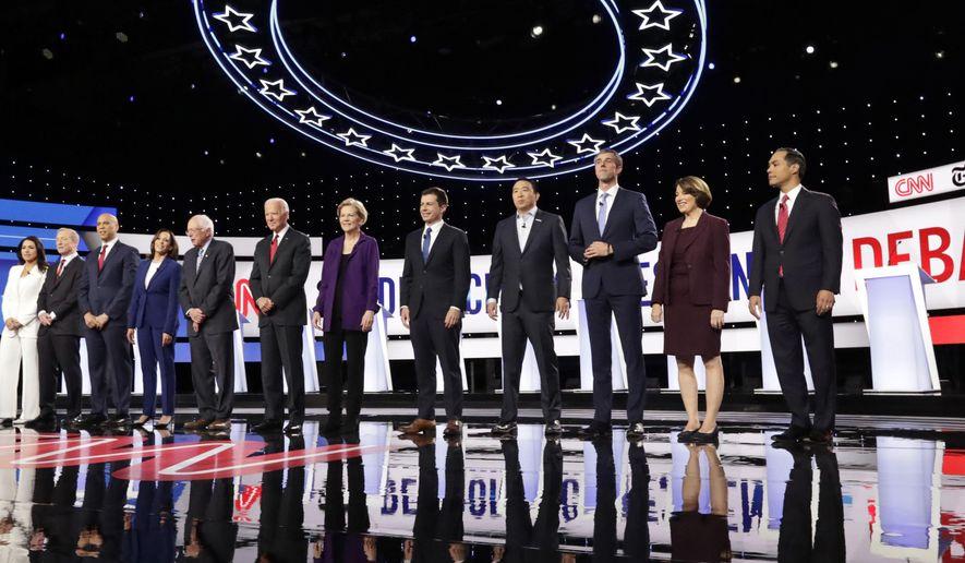 From left, Democratic presidential candidates, Rep. Tulsi Gabbard, D-Hawaii, businessman Tom Steyer, Sen. Cory Booker, D-N.J., Sen. Kamala Harris, D-Calif., Sen. Bernie Sanders, I-Vt., former Vice President Joe Biden, Sen. Elizabeth Warren, D-Mass., South Bend Mayor Pete Buttigieg, entrepreneur Andrew Yang, former Texas Rep. Beto O'Rourke, Sen. Amy Klobuchar, D-Minn., and former Housing Secretary Julian Castro stand on stage for a photo before a Democratic presidential primary debate hosted by CNN and The New York Times at Otterbein University, Tuesday, Oct. 15, 2019, in Westerville, Ohio. (AP Photo/Tony Dejak)