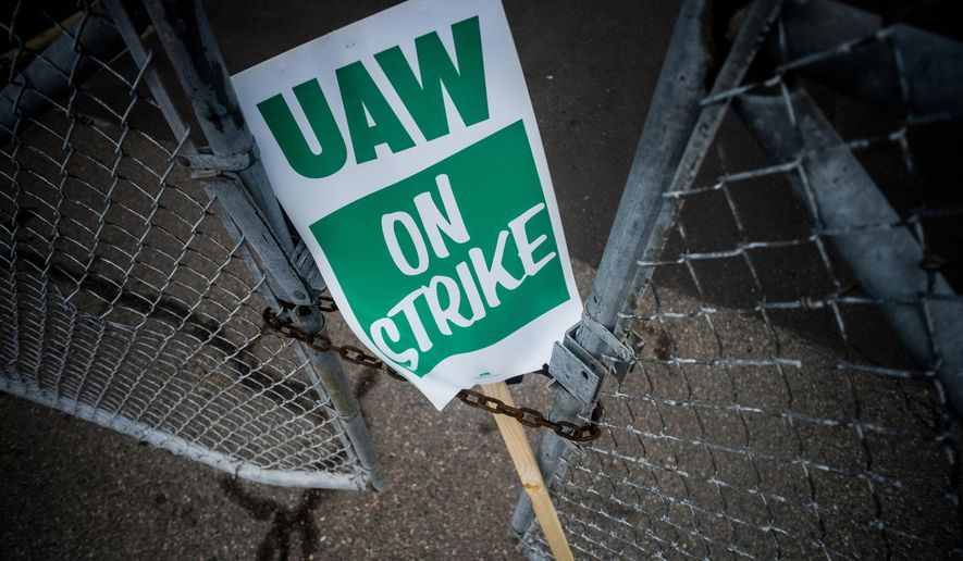 In this Sept. 16, 2019, file photo, a United Auto Workers strike sign rests between the chains of a locked gate entrance outside of Flint Engine Operations in Flint, Mich. (Jake May/The Flint Journal via AP, File)