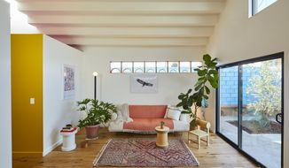 """This undated photo shows a converted garage project by Bunch Design in the Highland Park area of Los Angeles, Calif. In this converted garage project, long clerestory windows were placed high on the walls of a small living room. Afternoon light streams through a west-facing skylight, and a stepped ceiling creates more interesting light plays. """"The house sits in the middle of a dense residential neighborhood,"""" says Bo Sundius of Bunch Design, """"yet it feels airy and open."""" Sundius says they always think of how sun and light moving across space can be utilized to connect interiors to the outside world. (Bunch Design via AP)"""