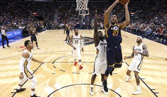 Utah Jazz center Rudy Gobert (27) shoots over New Orleans Pelicans forward Zion Williamson (1) during the second half of a preseason NBA basketball game in New Orleans, Friday, Oct. 11, 2019. (AP Photo/Tyler Kaufman)