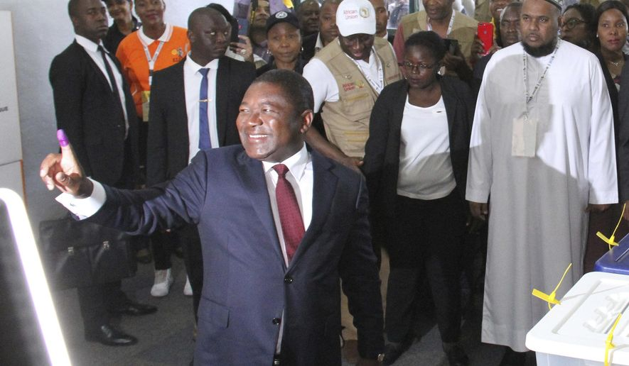 Mozambican President Felipe Nyusi poses at a polling station where he cast his vote in Maputo, Mozambique Tuesday, Oct. 15, 2019 in the country's presidential, parliamentary and provincial elections. Polling stations opened across the country with 13 million voters registered to cast ballots in elections seen as key to consolidating peace in the southern African nation. (AP Photo/Ferhat Momade)