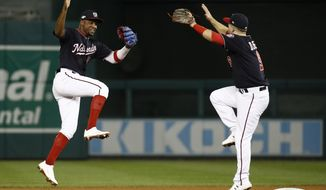 Washington Nationals' Victor Robles and Brian Dozier celebrate after Game 3 of the baseball National League Championship Series against the St. Louis Cardinals Monday, Oct. 14, 2019, in Washington. The Nationals won 8-1 to take a 3-0 lead in the series. (AP Photo/Patrick Semansky) ** FILE **