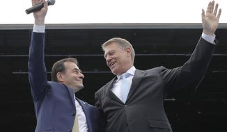 FILE- In this Saturday, May 18, 2019, file picture Liberal party President Ludovic Orban, left, and Romanian President Klaus Iohannis wave on stage during an European Parliament electoral rally in Bucharest, Romania. Romania's president has nominated, Tuesday, Oct. 15, 2019, Ludovic Orban of the center-right National Liberal Party to form a new government and become the country's next prime minister. (AP Photo/Vadim Ghirda, File)