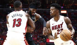 Miami Heat forward Jimmy Butler (22) dribbles the ball against San Antonio Spurs forward DeMarre Carroll (77) during the second half of an NBA preseason basketball game Tuesday, Oct. 8, 2019, in Miami. (AP Photo/Brynn Anderson)