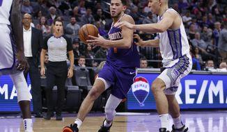 Phoenix Suns guard Devin Booker, left, drives to the basket against Sacramento Kings guard Bogdan Bogdanovic during the second half of an NBA preseason basketball game in Sacramento, Calif., Thursday, Oct. 10, 2019. (AP Photo/Rich Pedroncelli)