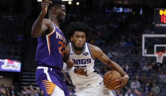 Phoenix Suns center Deandre Ayton, left, blocks he drive of Sacramento Kings forward Marvin Bagley III during the first quarter of an NBA preseason basketball game in Sacramento, Calif., Thursday, Oct. 10, 2019. (AP Photo/Rich Pedroncelli)