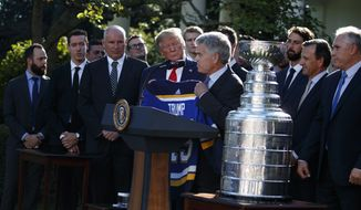 President Donald Trump is presented a team jersey by St. Louis Blues owner Tom Stillman during an event to honor the 2019 Stanley Cup Champion St. Louis Blues, in the Rose Garden of the White House, Tuesday, Oct. 15, 2019, in Washington. (AP Photo/Evan Vucci)