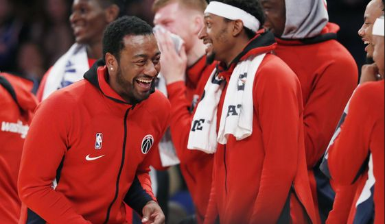 Washington Wizards guard John Wall, left, who is recovering from an Achilles injury, laughs as he watches from the bench with teammates during the waning moments of the team's preseason NBA basketball game against the New York Knicks in New York, Friday, Oct. 11, 2019. (AP Photo/Kathy Willens)