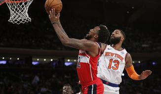 Washington Wizards guard Jordan McRae. left, goes up for a layup with New York Knicks forward Marcus Morris (13) defending during the first half of a preseason NBA basketball game in New York, Friday, Oct. 11, 2019. (AP Photo/Kathy Willens)