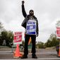 General Motors employee, and others are expected to continue picketing outside the GM Fabrication Division through Friday as bargainers for General Motors and the United Auto Workers iron out details of a tentative contract. (Associated Press)