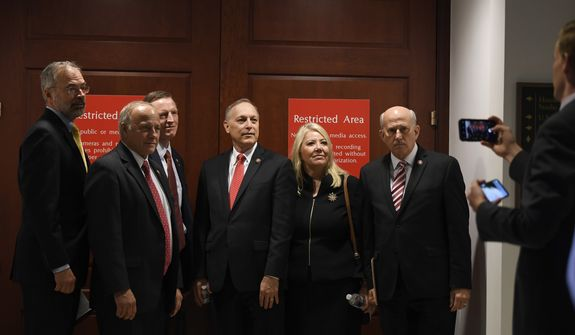 From left, Rep. Andy Harris, R-Md., Rep. Steve King, R-Iowa., Rep. Paul Gosar, R-Ariz., Rep. Andy Biggs, R-Ariz., Rep. Debbie Lesko, R-Ariz., and Rep. Louie Gohmert, R-Texas, pose for a group photo on Capitol Hill in Washington, Wednesday, Oct. 16, 2019, outside the room where people are interviewed for the impeachment inquiry. (AP Photo/Susan Walsh) **FILE**