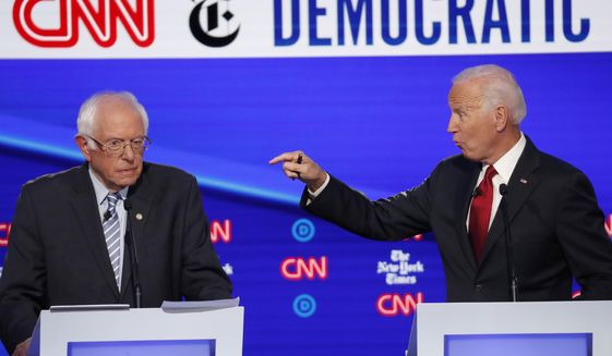 Democratic presidential candidate Sen. Bernie Sanders, I-Vt., left, listens as former Vice President Joe Biden speaks during a Democratic presidential primary debate hosted by CNN/New York Times at Otterbein University, Tuesday, Oct. 15, 2019, in Westerville, Ohio. (AP Photo/John Minchillo)