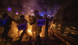Policemen in riot gear move past a burning barricade during clashes with protestors in Barcelona, Spain, Tuesday, Oct. 15, 2019. Spain's Supreme Court on Monday convicted 12 former Catalan politicians and activists for their roles in a secession bid in 2017, a ruling that immediately inflamed independence supporters in the wealthy northeastern region. (AP Photo/Emilio Morenatti)