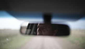 In this Oct. 9, 2019 photo, farmer Juan Rossi is reflected in his rearview mirror on the outskirts of Pergamino, Argentina. Farmers like Rossi are bracing for a return of interventionist policies if a populist ticket returns to power. Export restrictions under former President Cristina Fernandez triggered a revolt by farmers in 2008 in one of the world's top suppliers of grains. (AP Photo/Natacha Pisarenko)