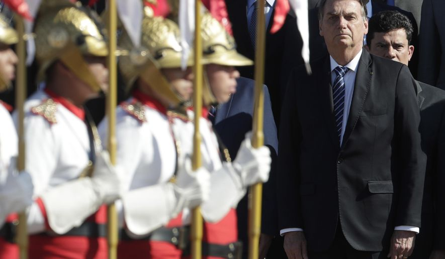 Brazil's President Jair Bolsonaro, right, with Justice Minister Sergio Moro standing behind him attend a Brazilian flag ceremony at the Alvorada Palace in Brasilia, Brazil, Tuesday, Oct.15, 2019. (AP Photo/Eraldo Peres)
