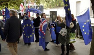 Anti-Brexit remain in the European Union supporters protest across the street from the Houses of Parliament in London, Tuesday, Oct. 15, 2019. A Brexit divorce deal is still possible ahead of Thursday's European Union summit but the British government needs to move ahead with more compromises to seal an agreement in the next few hours, the bloc said Tuesday. (AP Photo/Matt Dunham)