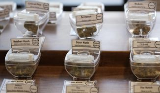 In this Wednesday, Oct. 9, 2019 photo, samples of marijuana, in tamper-proof containers that are secured with cables, are displayed at Evergreen Cannabis, a marijuana retail shop, in Vancouver, B.C. The nation has seen no sign of increases in impaired driving or underage use since Canada joined Uruguay as the only nations to legalize and regulate the sale of cannabis to adults _ those over 19 in most Canadian provinces. (AP Photo/Elaine Thompson)