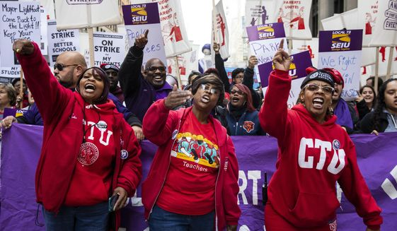 In this Oct. 14, 2019, file photo, members of the Chicago Teachers Union and SEIU Local 73 march through the Loop after a rally, three days before the unions could walk off the job on strike. (Ashlee Rezin Garcia/Chicago Sun-Times via AP) ** FILE **