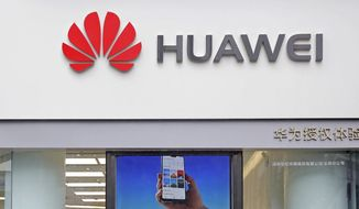 FILE - In this March 7, 2019 file photo, a logo of Huawei is displayed at a shop in Shenzhen, China's Guangdong province. Chinese tech giant Huawei has reported a double-digit rise in sales despite U.S. sanctions that threaten to disrupt its smartphone and network equipment businesses. Huawei Technologies Ltd. said Wednesday, Oct. 16, that its sales rose 24.4% in the first nine months of 2019 to 610.8 billion yuan ($86 billion). That was faster than the 23.2% gain reported for the first half.(AP Photo/Kin Cheung, File)