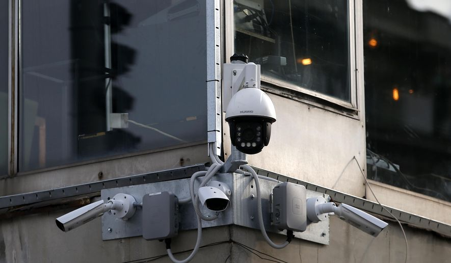 In this photo taken Sept. 25, 2019, high-tech video cameras hang from an office building in downtown Belgrade, Serbia. The cameras, equipped with facial recognition technology, are being rolled out across hundreds of cities around the world, particularly in poorer countries with weak track records on human rights where Beijing has increased its influence through big business deals. (AP Photo/Darko Vojinovic)