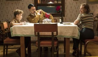 """This image released by Fox Searchlight Pictures shows, from left, Roman Griffin Davis, Taika Waititi and Scarlett Johansson in a scene from the WWII satirical film """"Jojo Rabbit."""" (Kimberley French/Fox Searchlight Pictures via AP)"""
