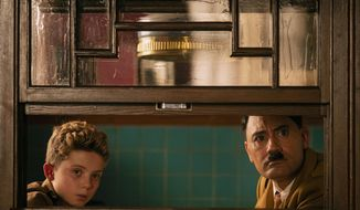 "This image released by Fox Searchlight Pictures shows, from left, Roman Griffin Davis and Taika Waititi in a scene from the WWII satirical film ""Jojo Rabbit."" (Kimberley French/Fox Searchlight Pictures via AP)"
