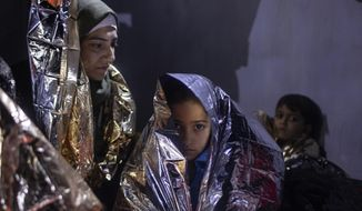 In this early Thursday, Sept. 26, 2019 photo, an Iraqi girl is wrapped in a thermal blanket after being transferred from a dinghy onto a Greek coast guard patrol boat during a rescue operation near the eastern Aegean Sea island of Samos. The 23 people from Syria, Iraq, Palestine and Iran had set out in the dinghy from nearby Turkey. They were taken to a camp on Samos. (AP Photo/Petros Giannakouris)