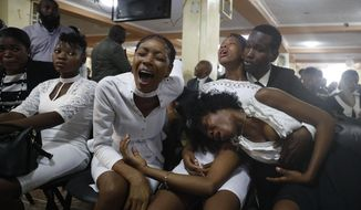 """Relatives of murdered community leader Josemano """"Badou"""" Victorieux mourn during Victorieux's funeral in Port-au-Prince, Haiti, Wednesday, Oct. 16, 2019. Family members plan to bury three of the people killed in recent violence related to protests calling for the resignation of President Jovenel Moise. Haiti has entered into a fifth week of deadly protests that have paralyzed the economy and shuttered schools. (AP Photo/Rebecca Blackwell)"""
