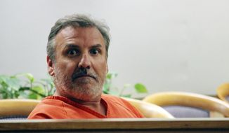 Brian Steven Smith looks out in the courtroom while waiting for his arraignment to start Wednesday, Oct. 16, 2019, in Anchorage, Alaska. A public defender entered not guilty pleas for Smith, who is accused of documenting the assault and murder of Kathleen Henry in an Anchorage hotel. (AP Photo/Mark Thiessen)